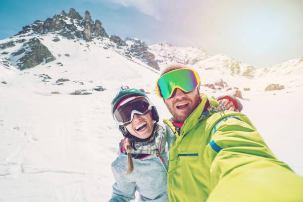 Zwei junge Erwachsene, die die Selfie von Skipisten in der Schweiz, Skiurlaub paar Touristen genießen Sie Schweizer Alpen und Ferien-Konzept – Foto