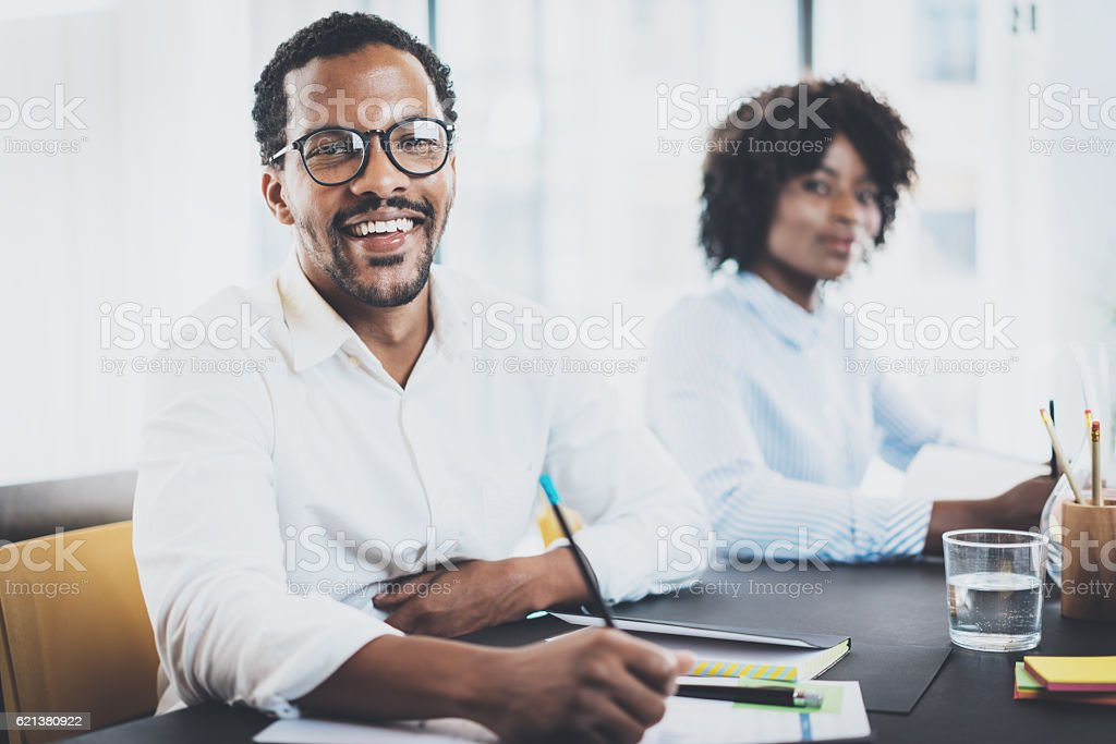 Two young african business people working together in a modern stock photo