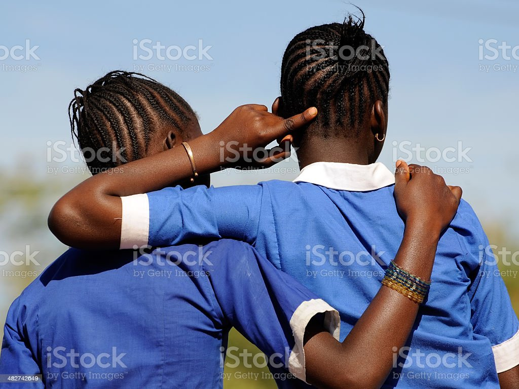Two young african school girls showing frienship stock photo