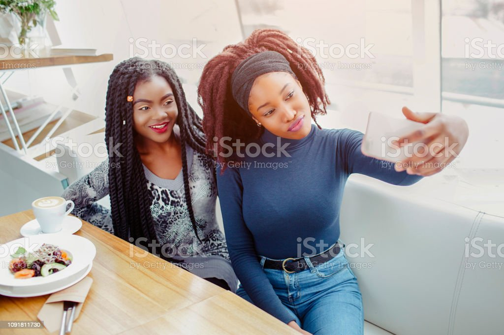 Two young african women pose on phone camera. They take selfie....