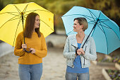 Two young and pretty women with umbrella in park