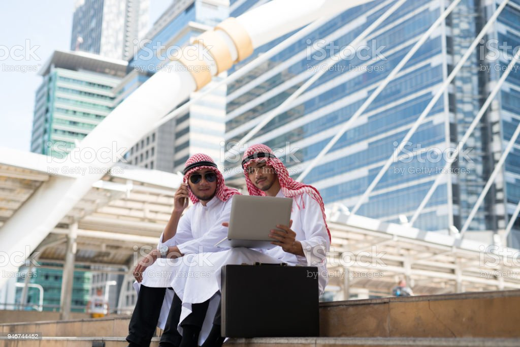 Two Young Arab businessman sit talking while working with laptop the background of bangkok city,  the business district with high building dazzled Two Young Arab businessman sit talking while working with laptop the background of bangkok city,  the business district with high building dazzled Adult Stock Photo
