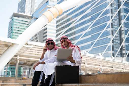 Two Young Arab Businessman Sit Talking While Working With Laptop The Background Of Bangkok City The Business District With High Building Dazzled Stock Photo - Download Image Now