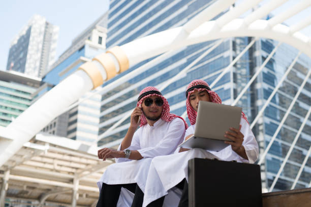 Two Young Arab businessman sit talking while working with laptop the background of bangkok city,  the business district with high building dazzled Two Young Arab businessman sit talking while working with laptop the background of bangkok city,  the business district with high building dazzled dazzled stock pictures, royalty-free photos & images