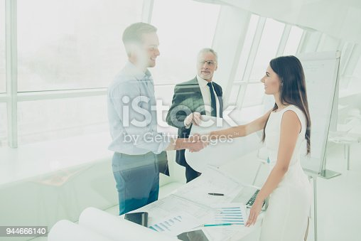 istock Two young architectors in formal wear  shaking hands and starting new project 944666140