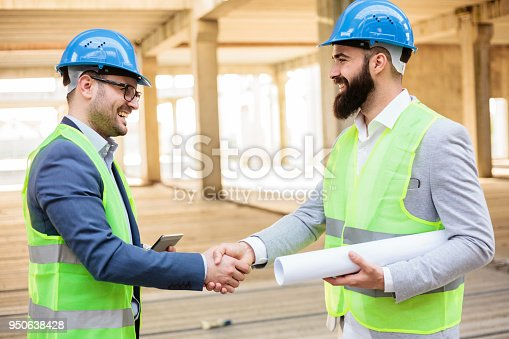 1166176793 istock photo Two young architects shaking hands 950638428