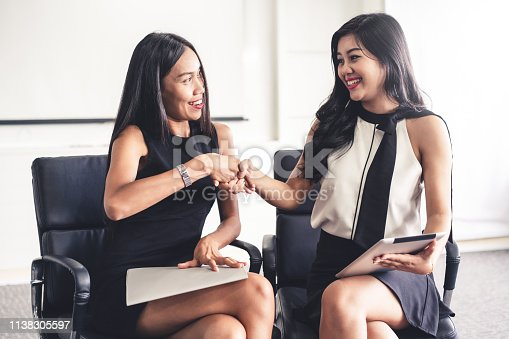 Two young Asian businesswomen do handshake in office. Business friends and community concept.