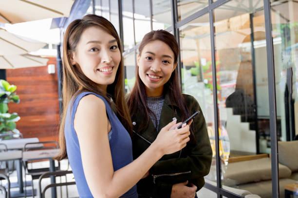 Zwei junge asiatische Freunde, die eine SMS im Freien lesen – Foto