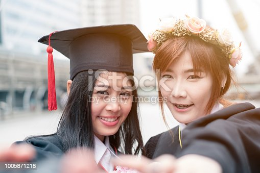 Two young asian girl reaching hands selfie a photo of Graduates of Bachelor's degree