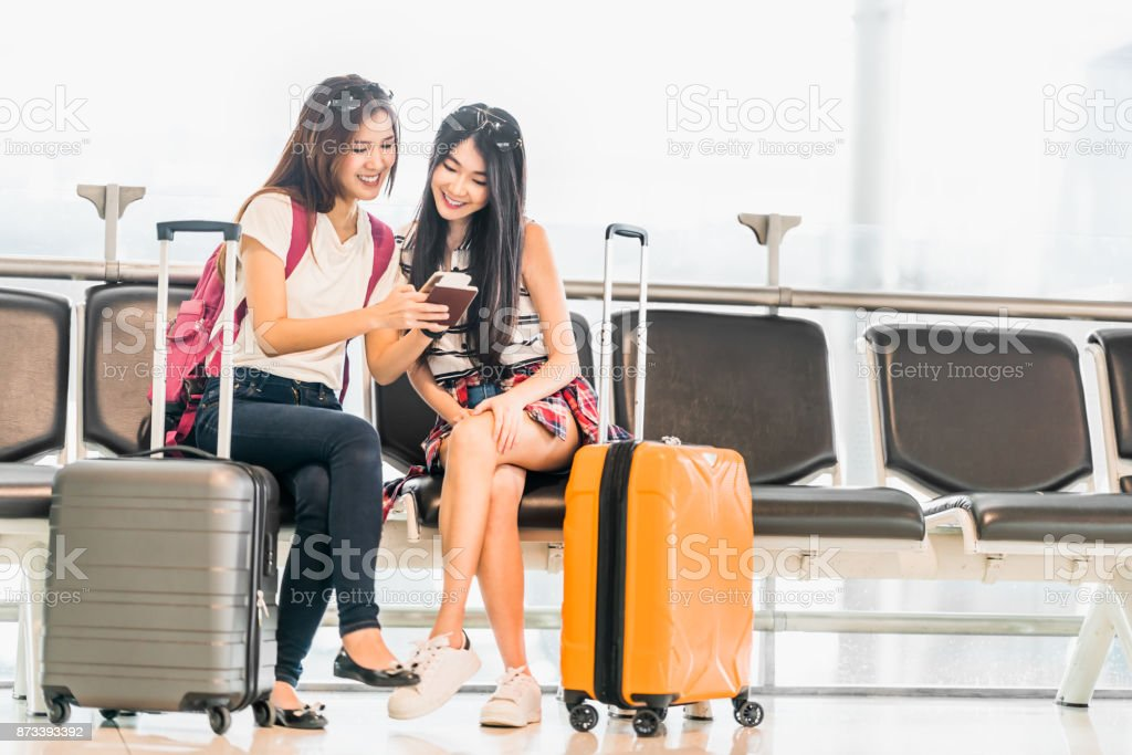 Two young Asian girl using smartphone check flight or web check-in, sit at airport waiting seat together. Air travel lifestyle, exciting summer vacation trip or mobile phone gadget application concept stock photo