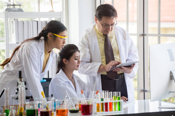 Two young  asian woman research scientist and senior man supervisor preparing test tube and analyzing microscope With Computer in  Laboratory . teamwork . three people stock photo