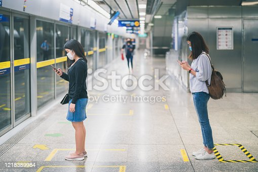 istock Two young asian woman wearing protective face mask stand in line with social distancing during waiting train in subway due to Coronavirus or COVID-19 outbreak situation in all of landmass in the world 1218389984