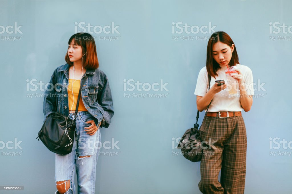 Two young Asian women in Bangkok downtown district, taking a break, texting on the cellphone, waiting zbiór zdjęć royalty-free