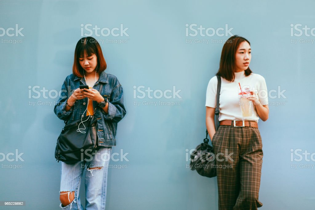 Two young Asian women in Bangkok downtown district, taking a break, texting on the cellphone, waiting royalty-free stock photo