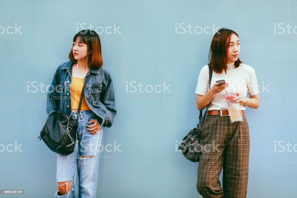 Two young Asian women in Bangkok downtown district, taking a break, texting on the cellphone, waiting stock photo