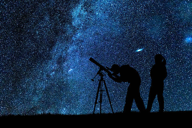 two young astronomers observing milky way - astronomie photos et images de collection