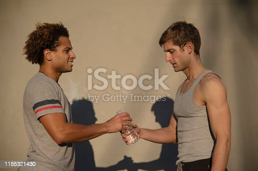 Two young athletes drinking bottled water. The portrait against the wall, with shadows, Santa Monica, California