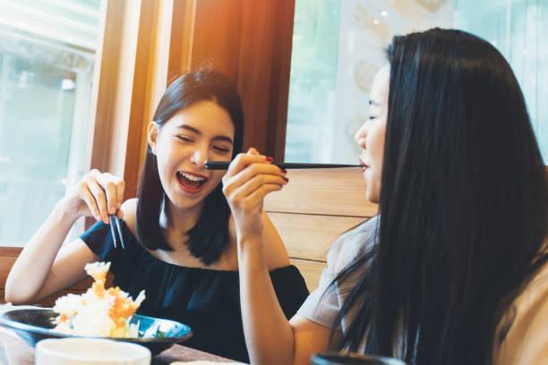 two young attractive asian women eating shrimp tempura japanese food at restaurant with happiness and joy - tempura imagens e fotografias de stock