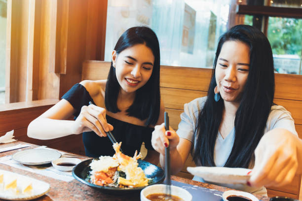 Two young attractive Asian women eating Shrimp Tempura Japanese food at restaurant with happiness and joy Two young attractive Asian women eating Shrimp Tempura Japanese food at restaurant with happiness and joy southeast asian ethnicity stock pictures, royalty-free photos & images