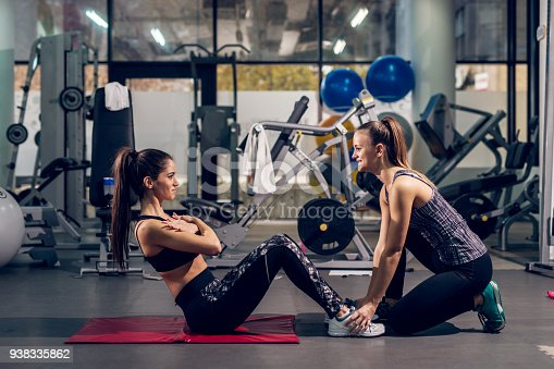 istock Two young attractive cheerful sporty active girls doing push ups in a team in the modern gym. 938335862