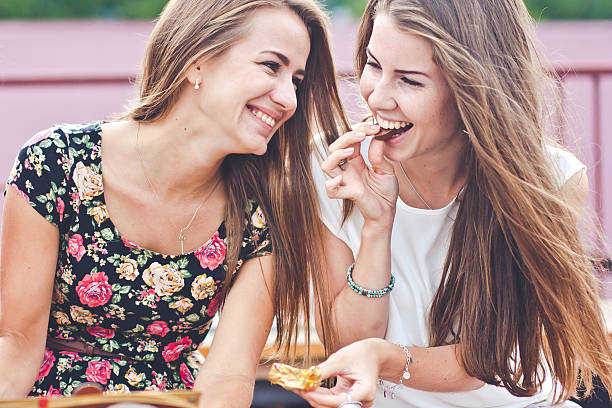Two young attractive females eat chocolates talk and laugh outdoors bildbanksfoto