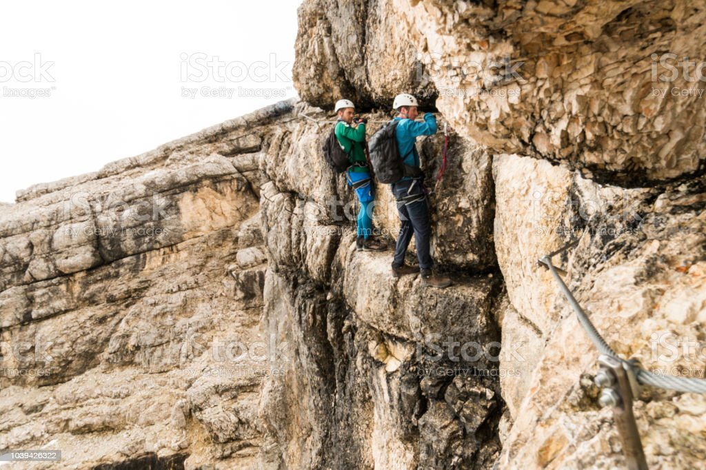 zwei junge attraktive männliche Bergsteiger auf sehr exponierten Klettersteig in den Dolomiten Italien - Lizenzfrei Abenteuer Stock-Foto