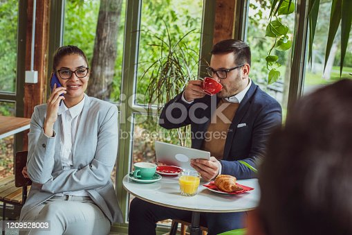 Two young, attractive, smartly dressed people having breakfast and coffee in a beautiful coffeehouse surrounded with greenery.