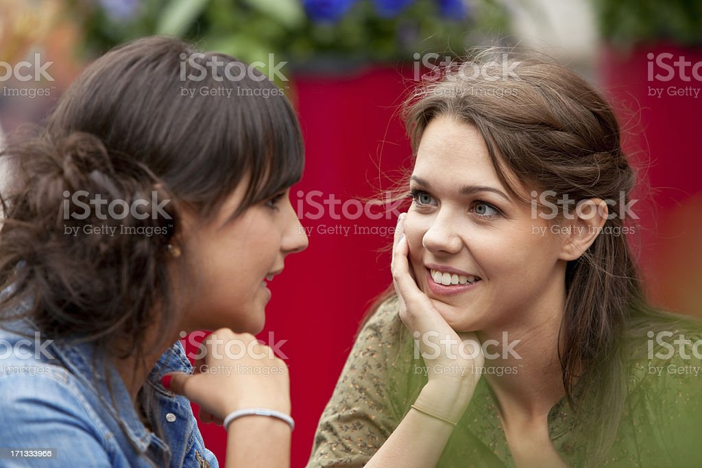 Two young  attractive women talking in street cafe royalty-free stock photo