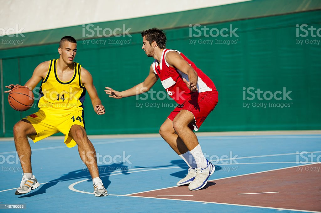 Two young basketball players at dribbling action stock photo