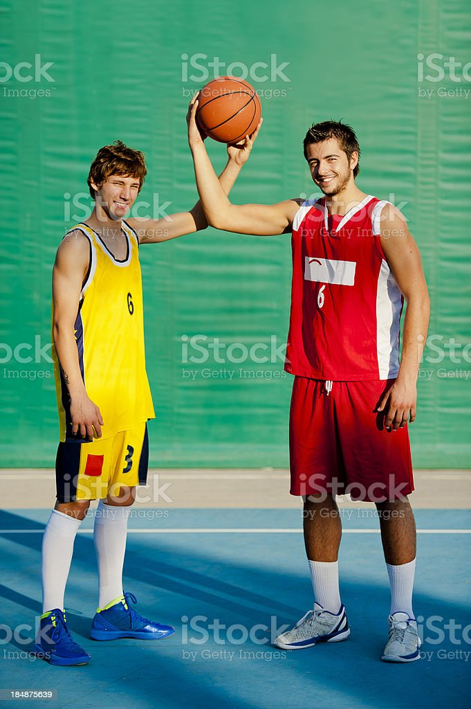 Two young basketball players posing with the ball stock photo