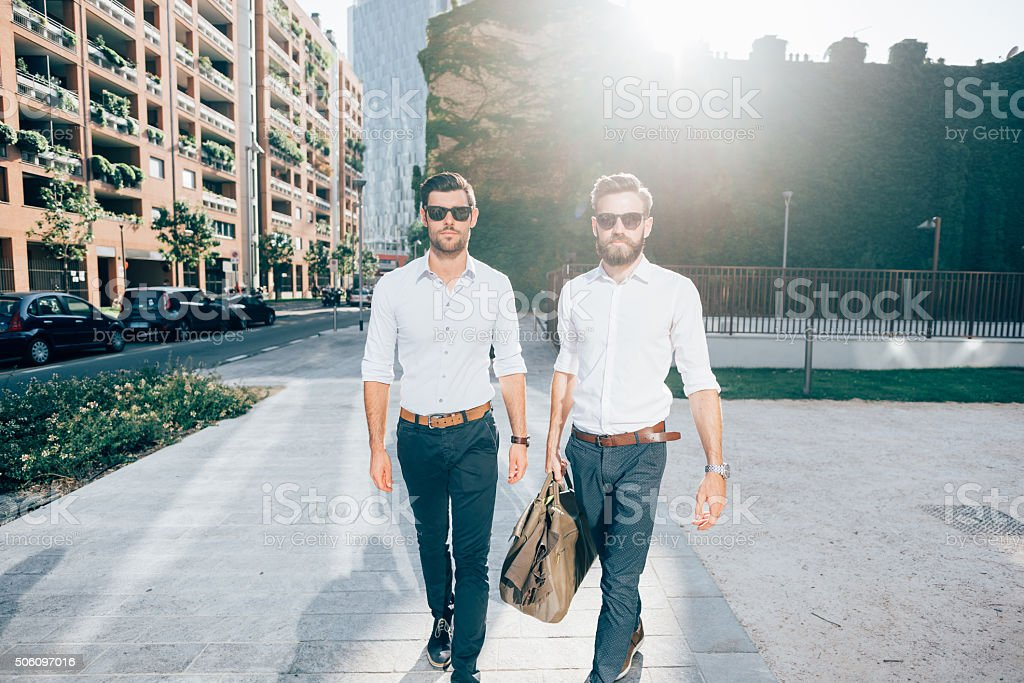 Two young bearded blonde and black hair modern businessman stock photo