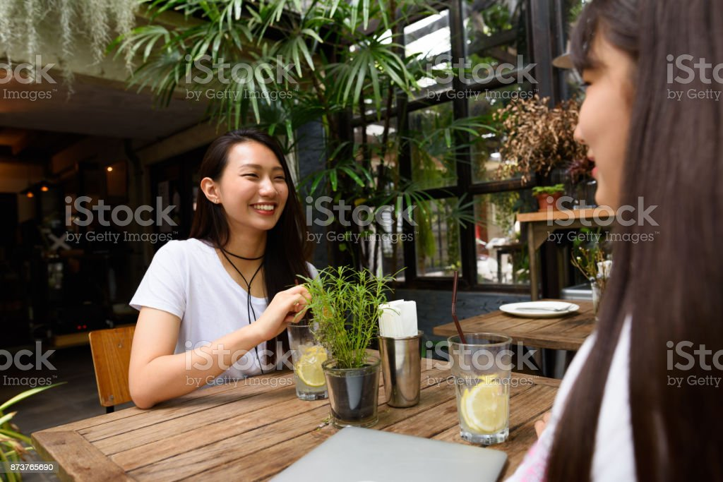 Two Young Beautiful Korean Women Friends Hanging Out Together At Outdoor Restaurant Stock Photo Download Image Now Istock