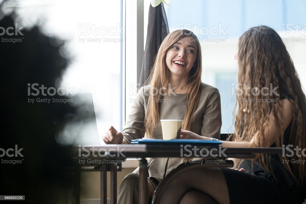 Two young beautiful women chatting in cafe stock photo