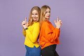 2つの若いブロンドの双子姉妹の女の子が背中に立ってカラフルな服を着て、指をパステルバイオレットブルーの背景に孤立した銃のように保ちます。人々の家族のライフスタイルの概念。コ