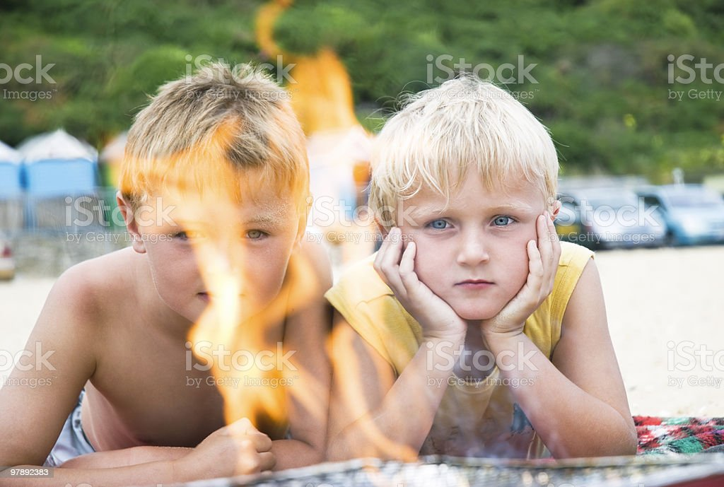 Two young boys at barbecue on beach. royalty-free stock photo