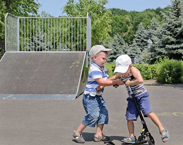 2 つの若い男の争い、スクーター - 兄弟 ストックフォトと画像