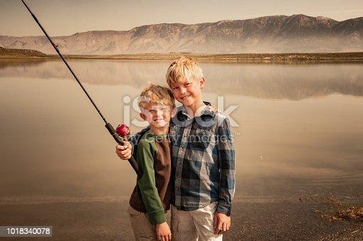 Two Young Boys Fishing On A Mountain Lake