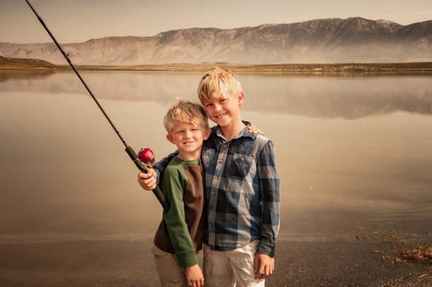 Two Young Boys Fishing On A Mountain Lake stock photo