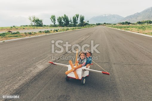 Two young boys dressed in flight caps and goggles get ready to fly a vintage toy airplane. Both boy are sitting in the plane ready for the thrill of takeoff. One is the pilot while the other is copilot. Seeing sights from the sky has never been better. Both boys are smiling and looking at the camera. Image taken in Utah, USA.