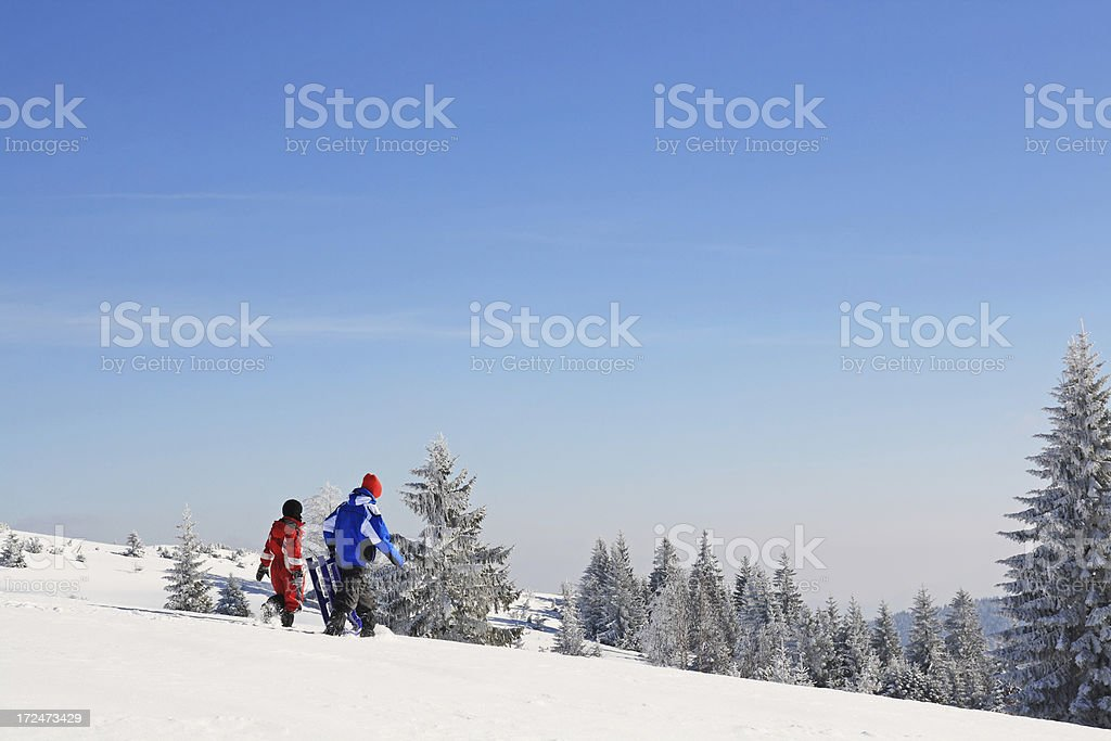 Two young boys go sledding royalty-free stock photo