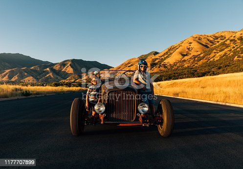 Two young boys in retro racing helmets and glasses are ready to race in their antique Model T Ford car. These next generation racers represent the revival of classic vintage cars.  They love hitting the road and the freedom cars give them. Photograph taken in Utah, USA.