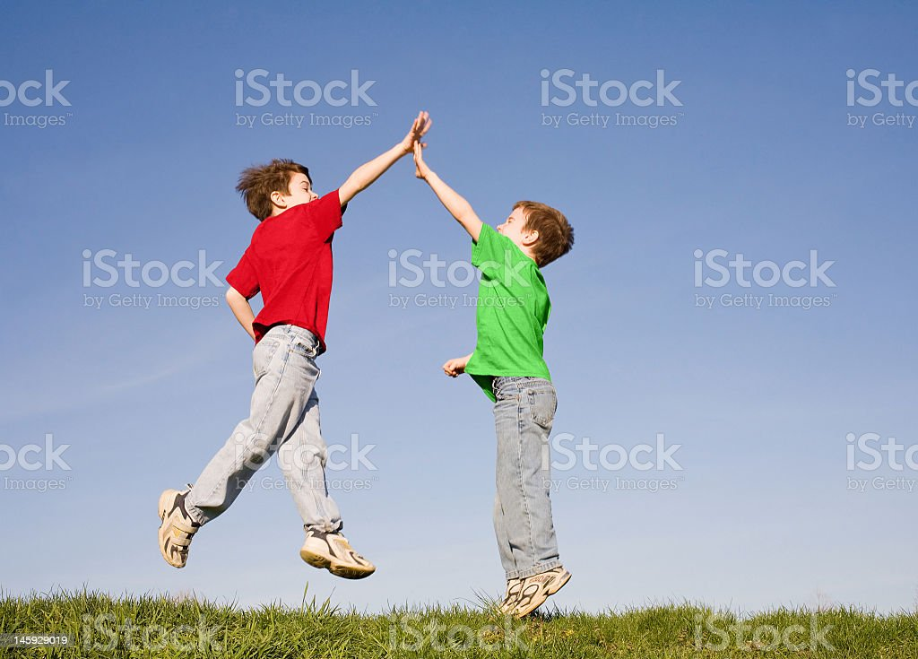 Two young boys jumping and giving a high five stock photo