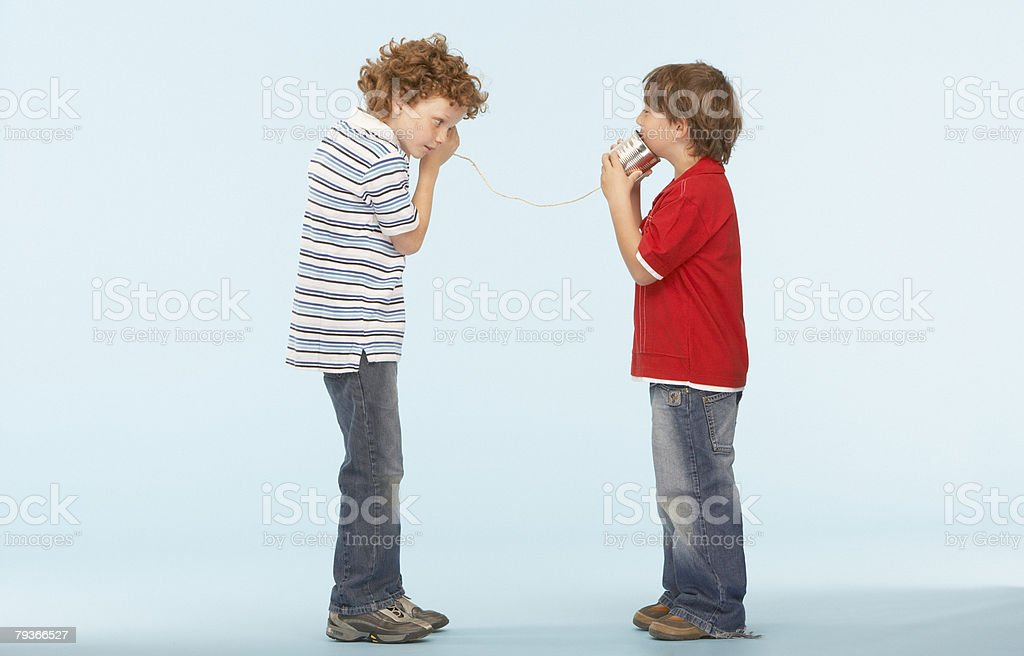 Two young boys playing with tin can phone 免版稅 stock photo
