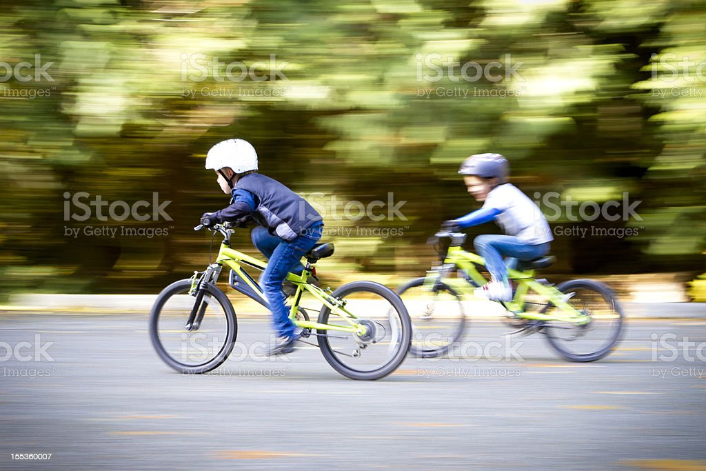 Two young boys racing their bikes. royalty-free stock photo