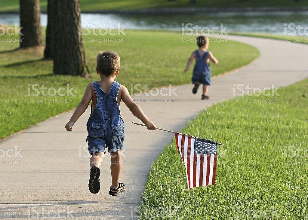 Two young boys running in a park with an American flag stock photo