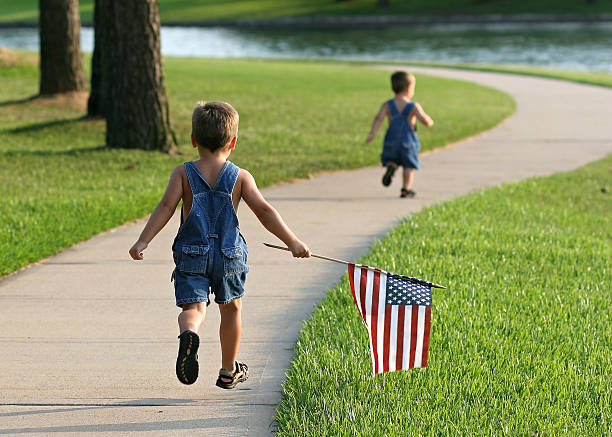Two young boys running in a park with an American flag These silly boys ran all the way around the lake with the flag on Flag Day! See similar images here: file_thumbview_approve.php?size=1&id=1643173 bunnylady stock pictures, royalty-free photos & images