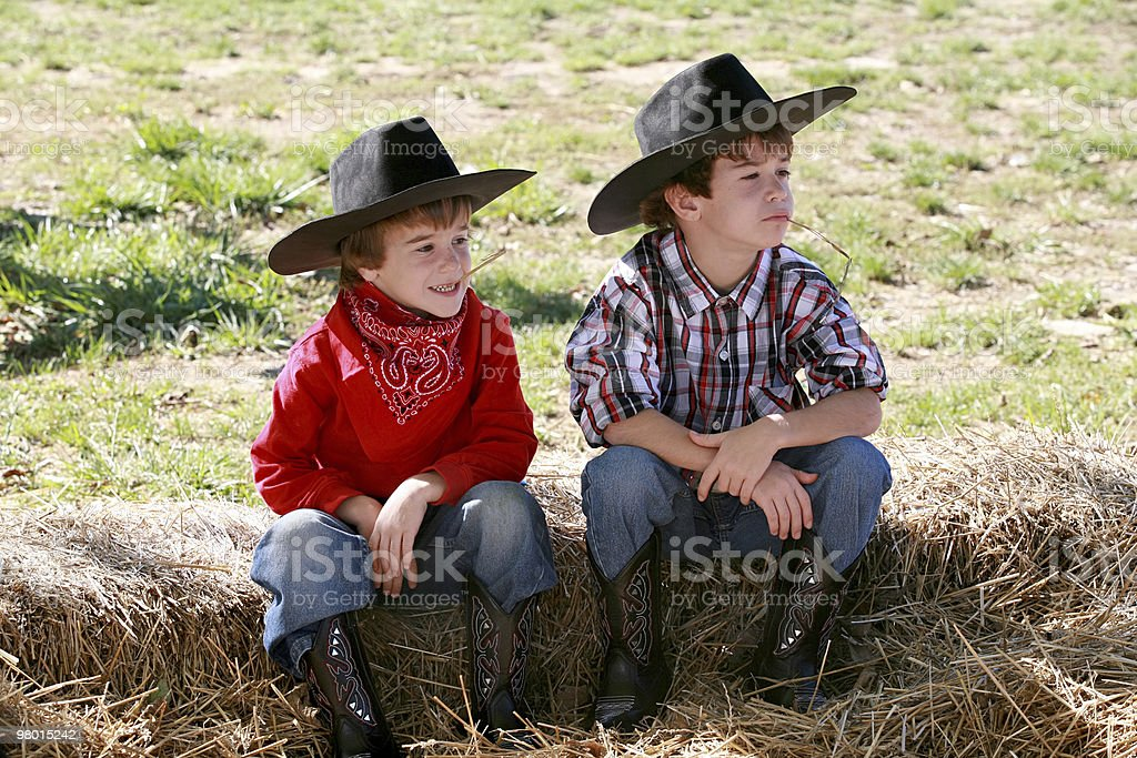 Two young boys sitting on log dressed as cowboys stock photo