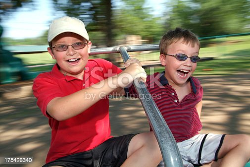 istock Two Young Boys Spinning Fast on a Merry Go Round 175426340