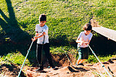 Two young boys using a rope to climb a hill