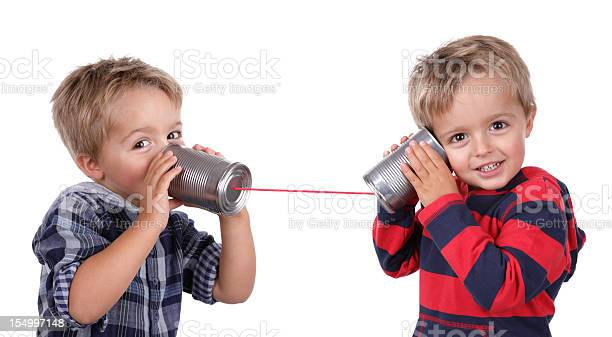 Two Young Boys Using Tin Cans And A String As A Telephone Stock Photo - Download Image Now